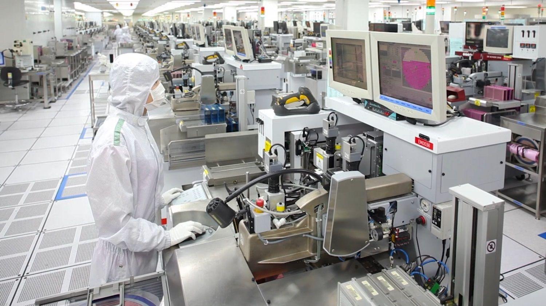 Un membre d'une équipe de production Micron portant une charlotte, une combinaison et un masque spécial pour ne pas polluer l'air d'une salle blanche avec des particules de poussière
