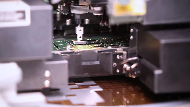 Une machine ramassant une puce dans le chargeur et la plaçant sur un circuit imprimé
