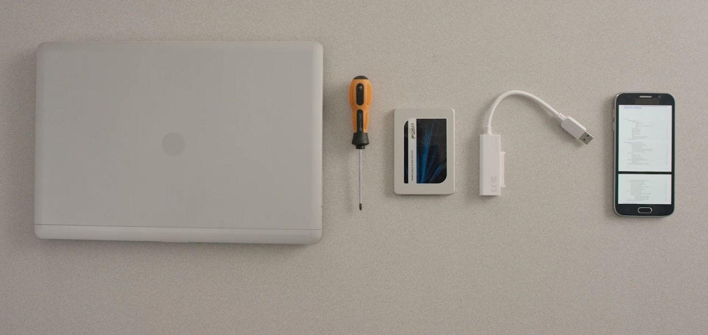 Un ordinateur portable, un SSD Crucial et le manuel d'utilisation de votre ordinateur sur téléphone sont disposés sur un bureau