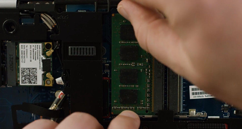 Une personne retirant un module de RAM de l'intérieur d'un ordinateur portable