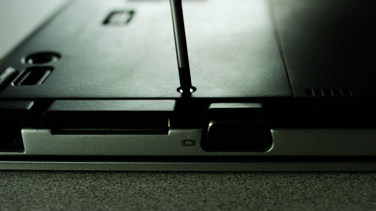 Un tournevis retirant une vis du dos d'un ordinateur