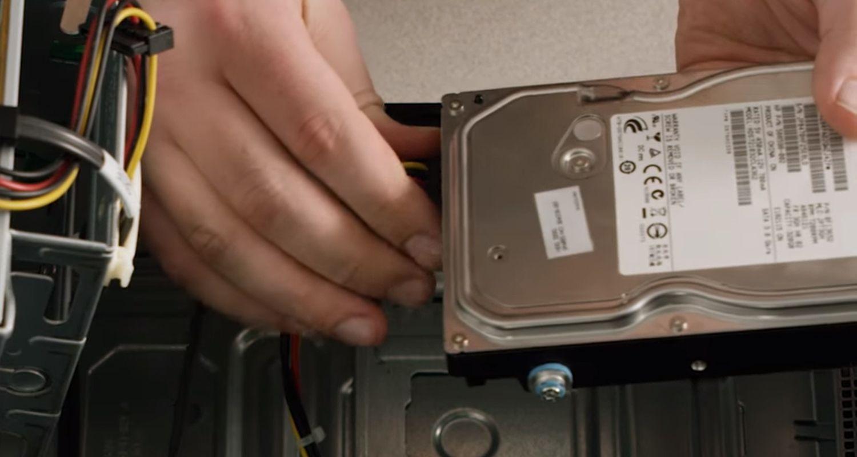 Une personne débranchant les câbles d'un disque de stockage d'un ordinateur de bureau